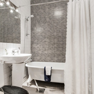 Scandi ensuite bathroom in Gothenburg with an alcove bath, a shower/bath combination, black and white tiles, white walls, a pedestal sink, white floors and a shower curtain.