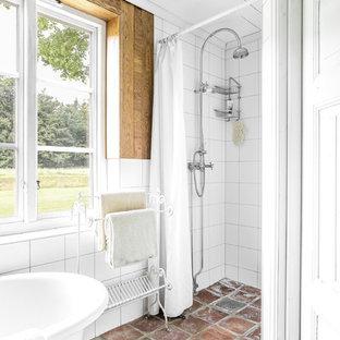 Bild på ett lantligt badrum, med klinkergolv i terrakotta och brunt golv
