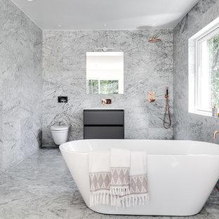 Modern inredning av ett stort badrum, med släta luckor, ett fristående badkar, en dusch/badkar-kombination, marmorkakel och marmorgolv