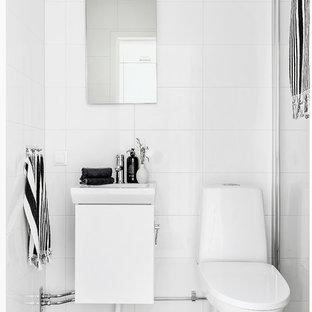 Minimalistisk inredning av ett badrum med dusch, med släta luckor, vita skåp, en hörndusch, vit kakel, vita väggar, ett konsol handfat, grått golv och dusch med gångjärnsdörr