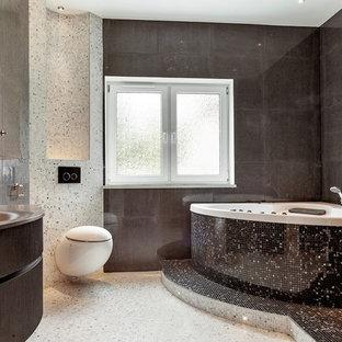 Ispirazione per una grande stanza da bagno padronale design con consolle stile comò, ante in legno bruno, vasca idromassaggio, WC sospeso, piastrelle nere, piastrelle grigie, piastrelle bianche, pareti grigie, lavabo integrato, piastrelle a mosaico, pavimento con piastrelle a mosaico e top in acciaio inossidabile