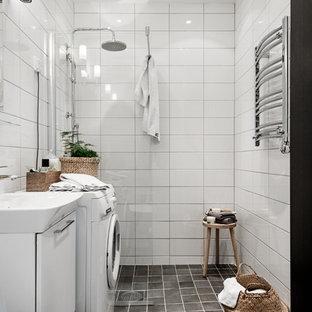 Idéer för mellanstora skandinaviska badrum, med släta luckor, vita skåp, vit kakel, svart golv, en toalettstol med hel cisternkåpa, vita väggar och ett fristående handfat