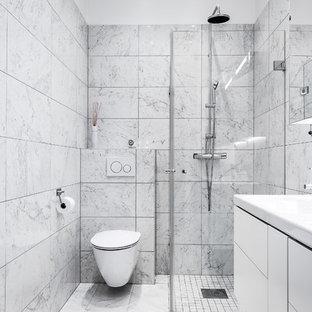 Exempel på ett mellanstort modernt badrum, med släta luckor, vita skåp, en hörndusch, en vägghängd toalettstol, svart och vit kakel, marmorkakel, vita väggar, marmorgolv och dusch med gångjärnsdörr