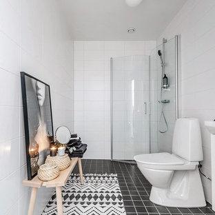 Exempel på ett minimalistiskt badrum med dusch, med vita skåp, våtrum, en toalettstol med separat cisternkåpa, vit kakel, keramikplattor, vita väggar och svart golv
