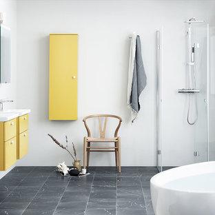 Esempio di una stanza da bagno con doccia nordica di medie dimensioni con ante lisce, ante gialle, vasca freestanding, pareti bianche, pavimento in marmo, lavabo sospeso, pavimento nero e porta doccia a battente