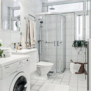 Idéer för att renovera ett nordiskt badrum med dusch, med en hörndusch, dusch med skjutdörr, släta luckor, vita skåp, en toalettstol med hel cisternkåpa, vit kakel, vita väggar, ett konsol handfat och vitt golv