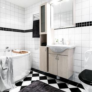 Exempel på ett mellanstort klassiskt en-suite badrum, med släta luckor, beige skåp, vita väggar, flerfärgat golv, ett fristående badkar, en toalettstol med hel cisternkåpa, svart och vit kakel och ett konsol handfat