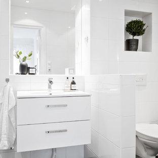 Inspiration för skandinaviska badrum med dusch, med släta luckor, vita skåp, en hörndusch, en vägghängd toalettstol, vit kakel, vita väggar, ett integrerad handfat, svart golv och med dusch som är öppen