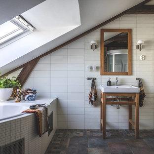 Inspiration för mellanstora medelhavsstil en-suite badrum, med ett hörnbadkar, vit kakel, cementkakel, vita väggar, ett konsol handfat och brunt golv