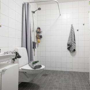 Exempel på ett minimalistiskt badrum med dusch, med släta luckor, vita skåp, en kantlös dusch, vit kakel, vita väggar, ett väggmonterat handfat, grått golv och dusch med duschdraperi