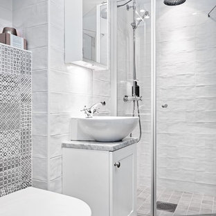 Diseño de cuarto de baño con ducha, escandinavo, de tamaño medio, con puertas de armario blancas, paredes blancas, lavabo sobreencimera, encimera de mármol, armarios estilo shaker, bañera con patas, ducha esquinera, baldosas y/o azulejos blancos, suelo beige y ducha con puerta con bisagras