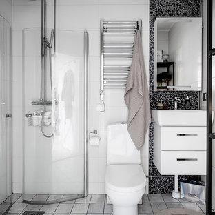 Inspiration för ett nordiskt badrum med dusch, med släta luckor, vita skåp, en hörndusch, en toalettstol med hel cisternkåpa, svart kakel, mosaik, vita väggar, ett konsol handfat, grått golv och dusch med gångjärnsdörr