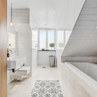 Неиссякаемый источник вдохновения для домашнего уюта: большая главная ванная комната в скандинавском стиле с ванной в нише, бежевой плиткой, белой плиткой, белыми стенами, подвесной раковиной, инсталляцией, керамогранитной плиткой, полом из известняка и бежевым полом