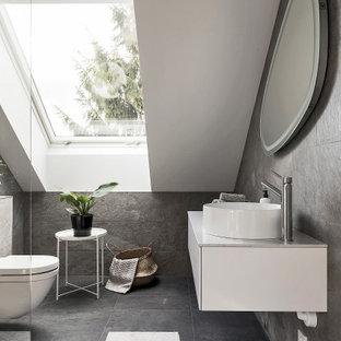 Inredning av ett minimalistiskt mellanstort vit vitt badrum med dusch, med släta luckor, vita skåp, en hörndusch, en toalettstol med hel cisternkåpa, grå kakel, ett fristående handfat och grått golv
