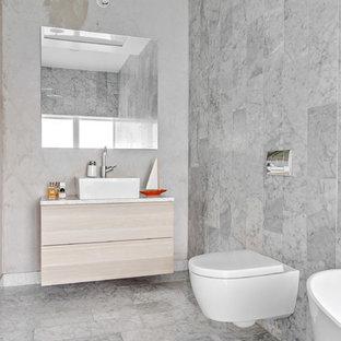 Idéer för att renovera ett stort skandinaviskt en-suite badrum, med släta luckor, skåp i ljust trä, en vägghängd toalettstol, grå kakel, marmorkakel, marmorgolv, ett fristående handfat, ett fristående badkar, våtrum, grå väggar, marmorbänkskiva, grått golv och med dusch som är öppen