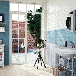 Immagine di una grande stanza da bagno padronale stile marinaro con lavabo a consolle, nessun'anta, pareti blu, ante bianche, piastrelle blu e piastrelle diamantate