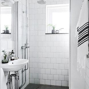 Exempel på ett minimalistiskt badrum med dusch, med en kantlös dusch, vit kakel, ett väggmonterat handfat, grått golv och dusch med gångjärnsdörr