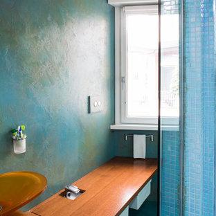 На фото: со средним бюджетом туалеты среднего размера в современном стиле с плоскими фасадами, белыми фасадами, раздельным унитазом, разноцветной плиткой, плиткой мозаикой, разноцветными стенами, полом из винила, настольной раковиной, столешницей из дерева и бирюзовым полом