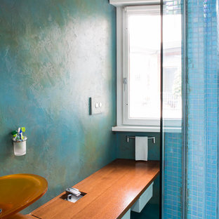 Design ideas for a medium sized contemporary cloakroom in Rome with flat-panel cabinets, white cabinets, a two-piece toilet, multi-coloured tiles, mosaic tiles, multi-coloured walls, vinyl flooring, a vessel sink, wooden worktops and turquoise floors.