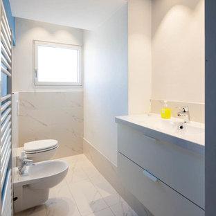 Idee per un bagno di servizio contemporaneo con ante lisce, piastrelle bianche, pareti bianche, pavimento con piastrelle in ceramica, lavabo integrato, bidè, lastra di pietra, ante grigie e pavimento bianco