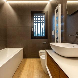 Exemple d'un très grand WC et toilettes tendance avec un placard avec porte à panneau encastré, des portes de placard en bois sombre, un WC séparé, un carrelage gris, des carreaux de porcelaine, un mur gris, un sol en bois clair, une vasque, un plan de toilette en surface solide, un plan de toilette blanc, meuble-lavabo suspendu et un plafond décaissé.