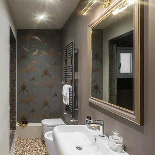 На фото: маленький туалет в современном стиле с биде, подвесной раковиной, разноцветным полом и разноцветными стенами с