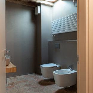Esempio di un bagno di servizio stile rurale di medie dimensioni con ante in legno chiaro, WC a due pezzi, pareti marroni, pavimento in terracotta, lavabo a bacinella, top in legno, pavimento multicolore e top marrone