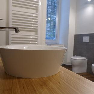 Идея дизайна: туалет среднего размера в современном стиле с открытыми фасадами, белыми фасадами, раздельным унитазом, белой плиткой, керамогранитной плиткой, белыми стенами, полом из ламината, настольной раковиной и столешницей из дерева