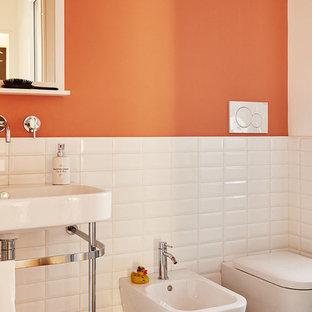 Immagine di un bagno di servizio minimalista con WC a due pezzi, piastrelle bianche, piastrelle in ceramica, pareti arancioni, pavimento con piastrelle in ceramica, lavabo a consolle e pavimento multicolore