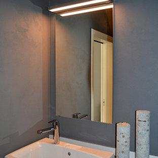 На фото: со средним бюджетом маленькие туалеты в стиле лофт с плоскими фасадами, серыми фасадами, серыми стенами, полом из керамогранита, накладной раковиной, столешницей из ламината и коричневым полом