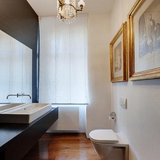 Foto di un bagno di servizio minimal con WC sospeso, pareti bianche, pavimento in legno massello medio, lavabo a bacinella e top nero