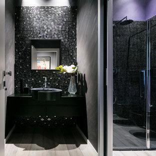 Idée de décoration pour un très grand WC et toilettes bohème avec un placard à porte affleurante, des portes de placard grises, un WC suspendu, un carrelage noir, un mur multicolore, un sol en bois foncé, un lavabo posé, un plan de toilette en bois et un sol gris.
