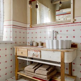 На фото: туалет в стиле кантри с фасадами островного типа, белой плиткой, красной плиткой, керамической плиткой, бежевыми стенами, полом из керамической плитки, настольной раковиной, столешницей из дерева, разноцветным полом, искусственно-состаренными фасадами и коричневой столешницей с