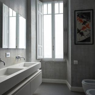 Неиссякаемый источник вдохновения для домашнего уюта: огромный туалет в современном стиле с стеклянными фасадами, белыми фасадами, раздельным унитазом, серыми стенами, подвесной раковиной, столешницей из искусственного камня, серым полом и белой столешницей