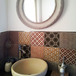 This is an example of a small contemporary cloakroom in Catania-Palermo with flat-panel cabinets, brown cabinets, a two-piece toilet, multi-coloured tiles, porcelain tiles, white walls, porcelain flooring, a vessel sink and laminate worktops.