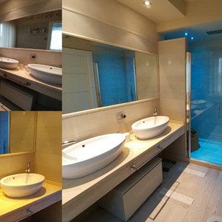 Esempio di un bagno di servizio minimalista di medie dimensioni con piastrelle grigie, parquet chiaro e top in travertino