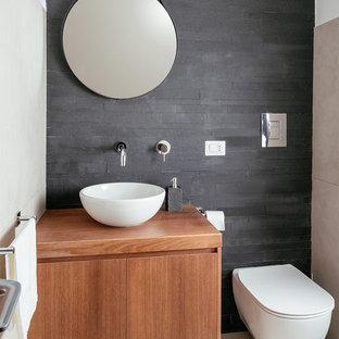 Cette photo montre un petit WC et toilettes tendance avec un placard à porte plane, des portes de placard en bois brun, un WC suspendu, un carrelage noir, du carrelage en ardoise, un sol en carrelage de porcelaine, une vasque, un plan de toilette en bois, un mur noir et un sol gris.