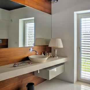 Modelo de aseo contemporáneo, de tamaño medio, con puertas de armario beige, sanitario de dos piezas, paredes marrones, suelo de terrazo, lavabo sobreencimera, suelo multicolor y encimeras beige