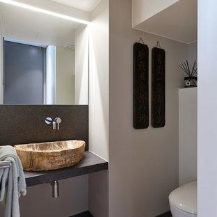 Idee per un bagno di servizio minimal con WC sospeso, pareti bianche, lavabo a bacinella, pavimento grigio e top nero
