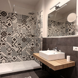 ローマの中くらいのトラディショナルスタイルのおしゃれなトイレ・洗面所 (淡色木目調キャビネット、黒い壁、磁器タイルの床、ラミネートカウンター、黒い床) の写真