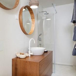 Неиссякаемый источник вдохновения для домашнего уюта: маленький туалет в скандинавском стиле с темными деревянными фасадами, белой плиткой, цементной плиткой, белыми стенами, бетонным полом, столешницей из дерева, белым полом и коричневой столешницей