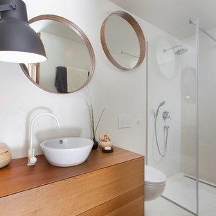 Стильный дизайн: маленький туалет в скандинавском стиле с темными деревянными фасадами, белой плиткой, цементной плиткой, белыми стенами, бетонным полом, столешницей из дерева, белым полом и коричневой столешницей - последний тренд