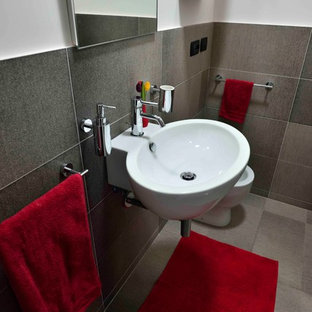 Idee per un piccolo bagno di servizio contemporaneo con ante lisce, ante rosse, WC a due pezzi, piastrelle grigie, piastrelle in gres porcellanato, pareti bianche, pavimento in gres porcellanato, lavabo sospeso e pavimento grigio