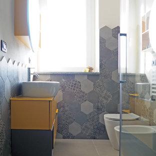Diseño de aseo moderno, pequeño, con armarios con paneles lisos, puertas de armario amarillas, bidé, baldosas y/o azulejos grises, baldosas y/o azulejos de porcelana, paredes blancas, suelo de baldosas de porcelana, lavabo sobreencimera, suelo gris y encimeras amarillas