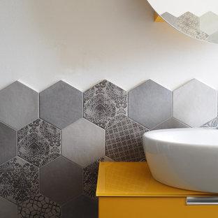 На фото: маленький туалет в стиле модернизм с плоскими фасадами, желтыми фасадами, биде, серой плиткой, керамогранитной плиткой, белыми стенами, полом из керамогранита, настольной раковиной, серым полом и желтой столешницей с