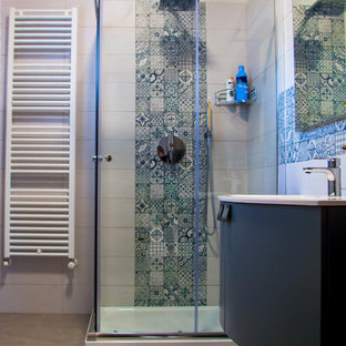 他の地域の小さいラスティックスタイルのおしゃれなトイレ・洗面所 (フラットパネル扉のキャビネット、青いキャビネット、分離型トイレ、マルチカラーのタイル、磁器タイル、磁器タイルの床、壁付け型シンク、ガラスの洗面台、グレーの床) の写真