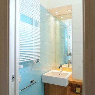 Идея дизайна: маленький туалет в современном стиле с плоскими фасадами, фасадами цвета дерева среднего тона, унитазом-моноблоком, синей плиткой, керамической плиткой, белыми стенами, полом из керамической плитки, накладной раковиной, столешницей из дерева и синим полом