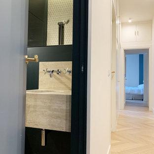 Aménagement d'un WC et toilettes avec un WC suspendu, un sol en bois clair, un lavabo posé, un plan de toilette en travertin, meuble-lavabo suspendu et du papier peint.