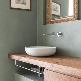 Foto di un bagno di servizio design con ante lisce, ante in legno scuro, pareti grigie, lavabo a bacinella e top in legno