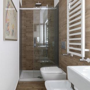 На фото: маленький туалет с плоскими фасадами, светлыми деревянными фасадами, инсталляцией, коричневой плиткой, удлиненной плиткой, белыми стенами, полом из керамогранита, подвесной раковиной и коричневым полом с